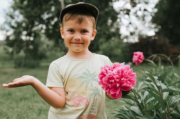 Россия, июнь 2020 года - портрет милого трогательного четырехлетнего мальчика с цветущим розовым пионом в деревенском саду в сельской местности летом