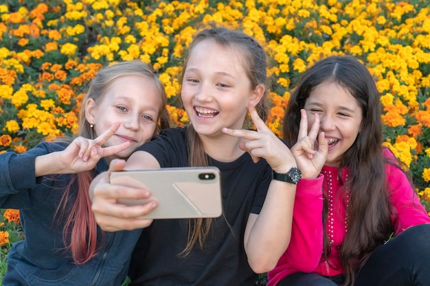 Russia, kazan - august 8, 2019: three teen girls take a selfie on a sunny day and laugh. girls are showing victory sign with their fingers.
