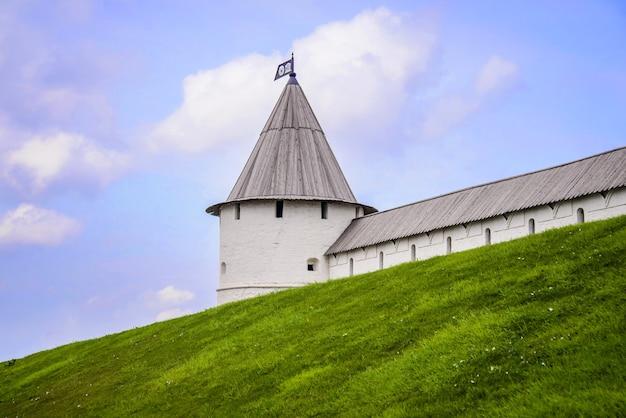 Россия, казань, 18 июля 2018: белая боковая башня и стена казанского кремля на фоне голубого неба и зеленой травы