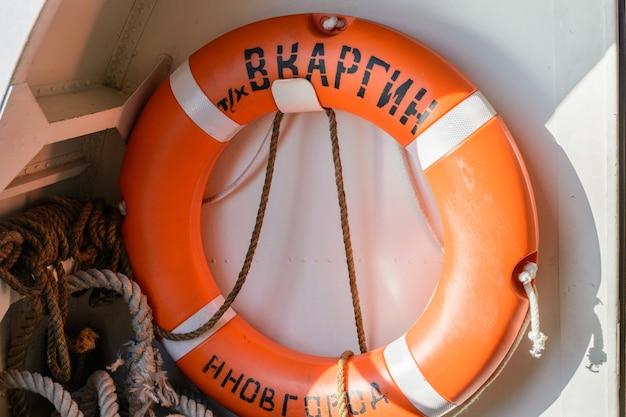Россия, казань - 12 сентября 2020 года. спасательный круг на корабле. надпись: «в. каргин» и «нижний новгород». река волга в республике татарстан.