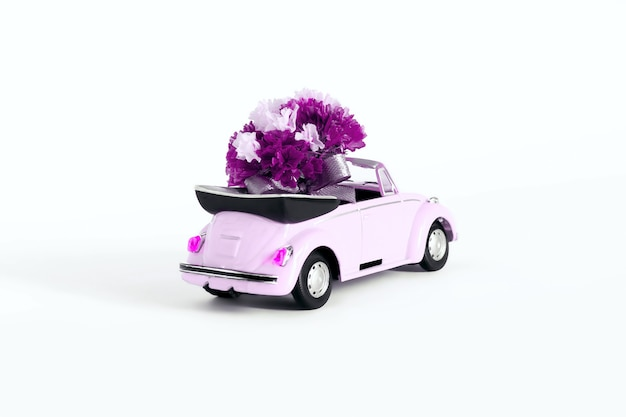 Russia. moscow. 07.02.2021 pink car with a bouquet of flowers on a white background. holiday concept, transportation.