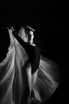 Russia, moscow, october 1, 2017: female gymnast posing on a black background and white cloth. art photo of a female gymnast. black and white photo