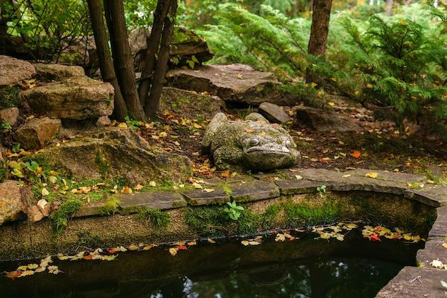 Россия, пермь - 9 сентября 2019 года: элемент ландшафтного дизайна, каменная садовая скульптура жабы возле водоема