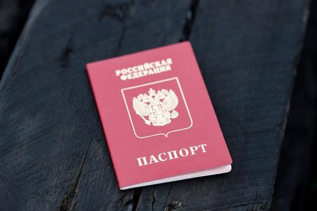 Паспорт россии лежит на обгоревшей деревянной балке. сгоревший дом. фото высокого качества