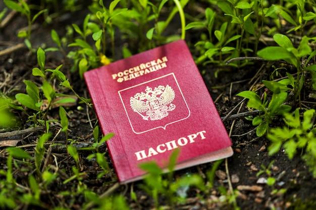 Паспорт россии лежит на земле в природе. утраченный документ. фото высокого качества