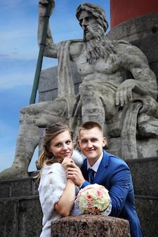 러시아, 상트 페테르부르크, 신부와 신랑이 조각에 맞서 로스트 랄 기둥 근처에 서 있습니다.