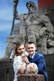 Russia, saint-petersburg, bride and groom stand near rostral column, against the sculpture.