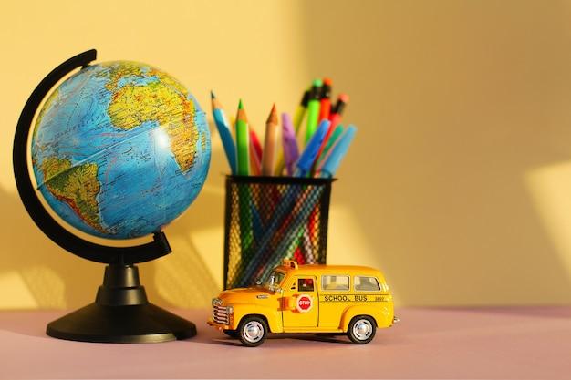 Россия, санкт-петербург 30 июля 2021 года: концепция образования и возвращение в школу. канцелярские товары в стакане, глобус и школьный автобус игрушечный автомобиль на столе на желтом фоне.