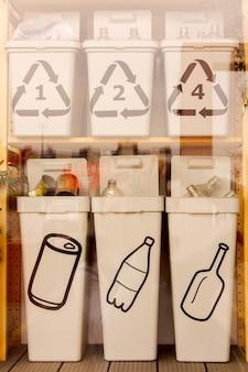 ロシア、サンクトペテルブルク2021年5月16日:自宅で廃棄物を分別する場所を組織した例。カテゴリ別のコンテナを備えたラック。ライフスタイルにおける環境にやさしい実践