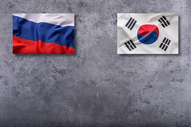 Russia and soutth korea flags. russia and south korea flag on concrete background.