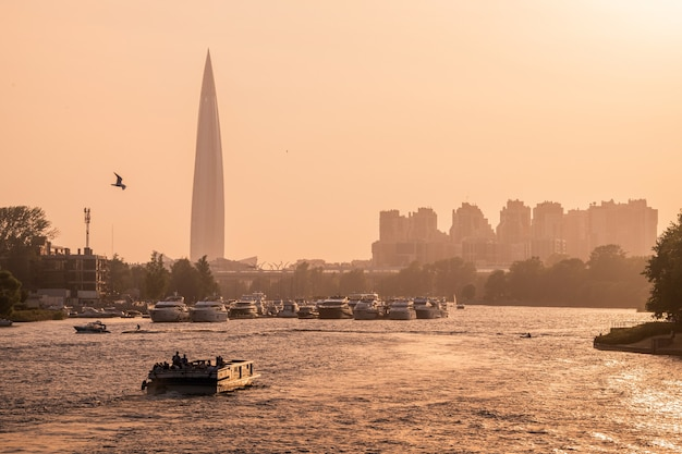 Россия, санкт-петербург. вид на башню газпрома, стоянку яхт и катеров в устье невы во время заката.