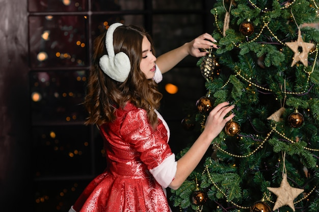 Russia, togliatti - november 13, 2018: christmas characters snow maiden. girl in a christmas costume decorates the christmas tree
