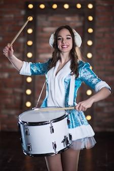 ロシア、トグリアッティ-2018年11月13日:クリスマスの雪の乙女キャラクターがスタジオでドラムを演奏