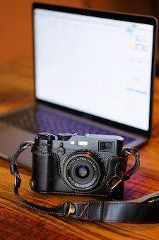 Russia, tyumen, 02.12.2019. a fujifilm camera in a black leather case, on a dark wooden table. next to the laptop. workplace and accessories of the photographer or a freelancer. copy paste text.