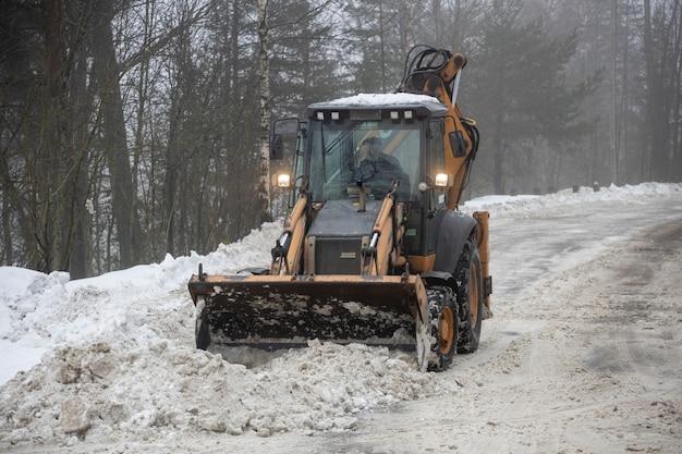ロシア。ヴィボルグ2020年2月27日トラクターに乗った男が街の通りから雪を取り除きます。高品質の写真