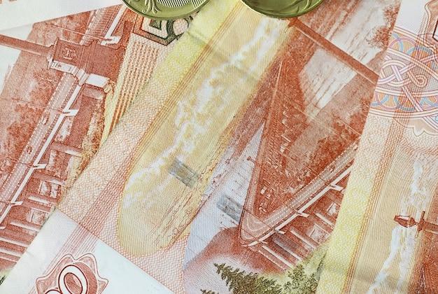 Банкноты и монеты россии «рубли». банкнота с надписью «пять тысяч рублей» и монеты номиналом 5 и 10 рублей. фон из денег.