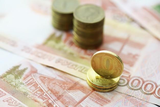 ロシアの紙幣と硬貨は「ルーブル」です。 「5000ルーブル」と書かれた紙幣と5ルーブルと10ルーブルの硬貨。お金で作られた背景。