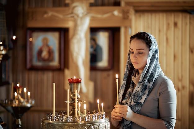 Русская красивая кавказская женщина с рыжими волосами и платком на голове в православной церкви