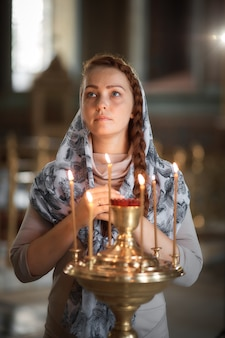 Russian beautiful caucasian woman with red hair and a scarf on her head is in the orthodox church, lights a candle and prays in front of the icon.