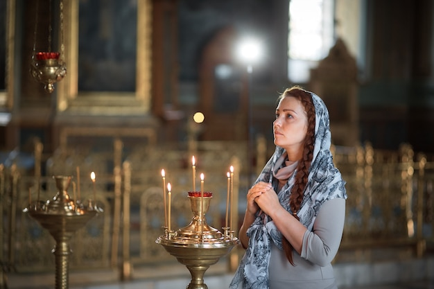 Russian beautiful caucasian woman with red hair and a scarf on her head is in the orthodox church