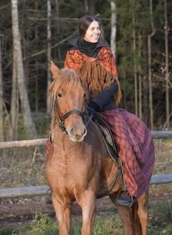 森の背景に馬に乗ってロシアの美しい少女。