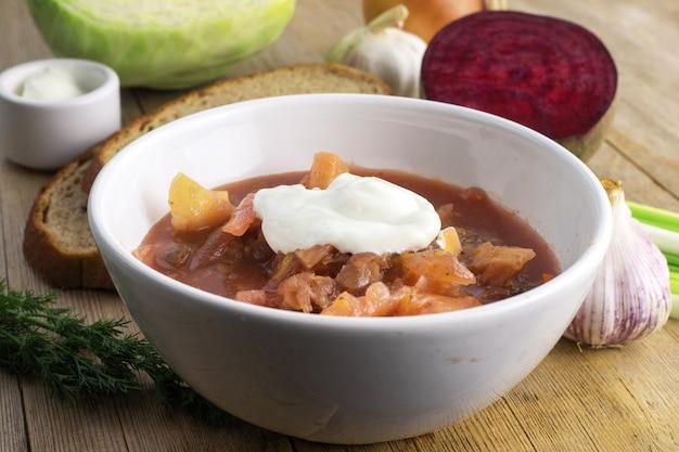 木製のテーブルの上の白いボウルにロシアのビートルート赤いスープをクローズアップ