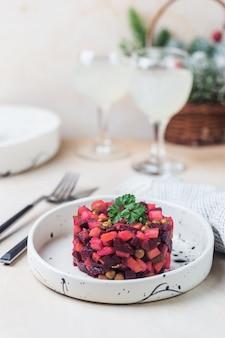 Винегрет из салата из русской свеклы в белой тарелке на светлом фоне