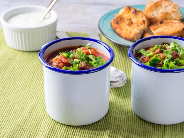 Russian beetroot soup borscht in enamel mugs