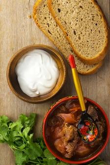 木製のテーブルトップビューに伝統的なパターンのスプーンとボウルにロシアのビートルートスープ