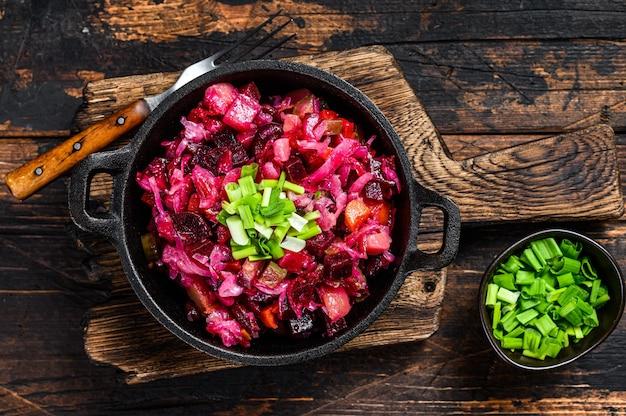 Русская свекла овощной салат винегрет на сковороде. деревянный фон. вид сверху.