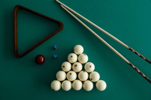 Russian billiard balls, cue, triangle, chalk on a table. green cloth. top view