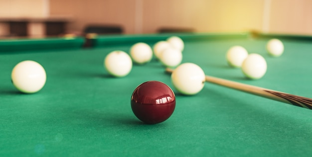 Russian billiard table with balls and cue sticks.