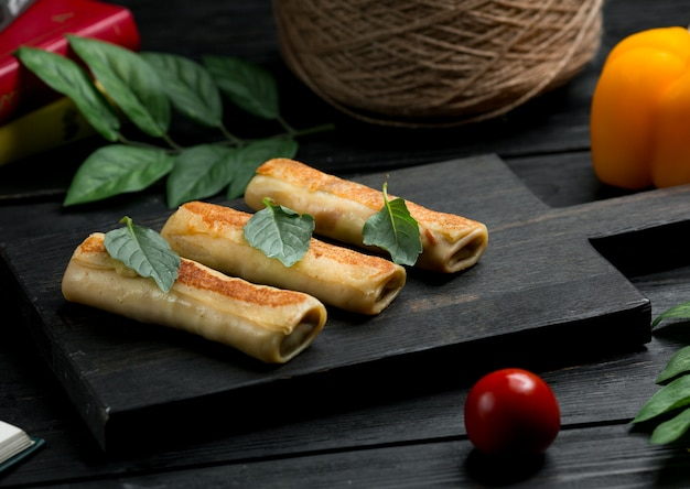 Russian blinchik crepes with oregano leaves and tomato
