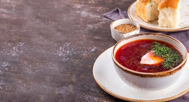 サワークリームとパンとロシアのボルシチ。ビートルートスープ。コピースペース、上面図