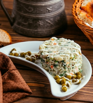 Russian capital salad with peas on the table