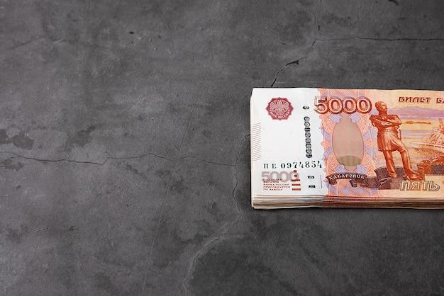 5000ルーブルのロシアの現金紙幣、バンドルは灰色の背景に掛かっています。
