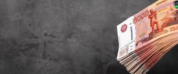 Наличные российские банкноты пяти тысяч рублей, пачка висит на сером фоне.