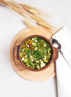 クワスと野菜とロシアの冷たいオクローシカは、木製のスタンドの陶器のカップに立っています