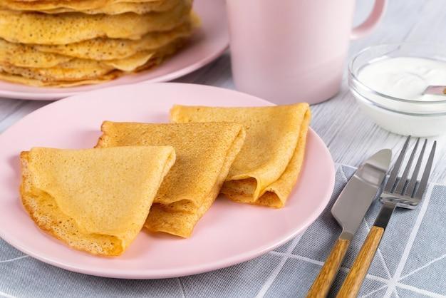 ピンクのプレートにロシアのクレープやパンケーキ