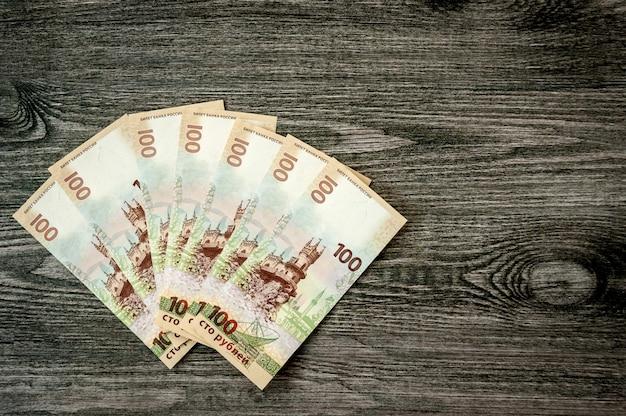 Банкноты российского крымского рубля, деньги на столе из темного дерева