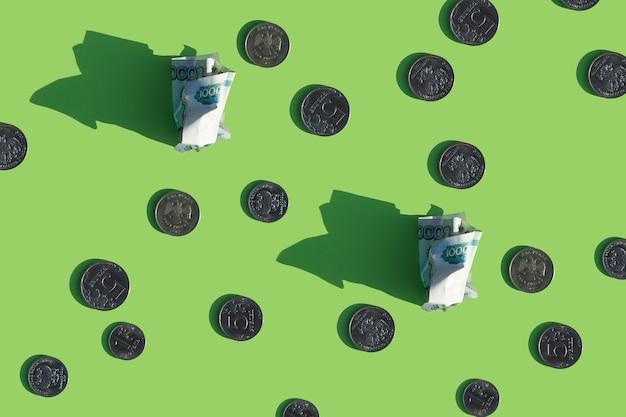Наличные деньги в российской валюте и монеты рублей на зеленом фоне