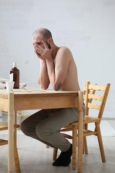 Русский пьяный сидит за столом и грустит с закрытым лицом.