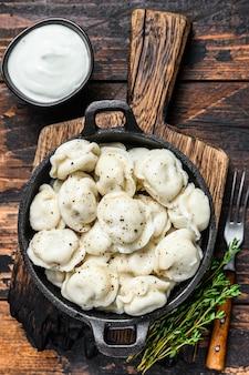 러시아 만두 pelmeni와 쇠고기와 돼지 고기. 어두운 나무 테이블. 평면도.