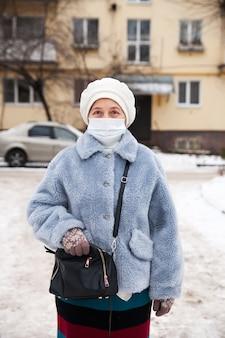 Русская пожилая старшая женщина в медицинской защитной маске зимой на улице