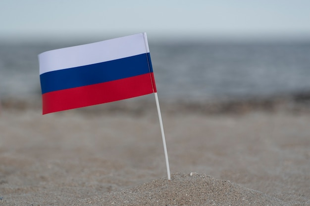 Russian flag on the beach. summer vacation at sea. tricolor flag of white blue red.