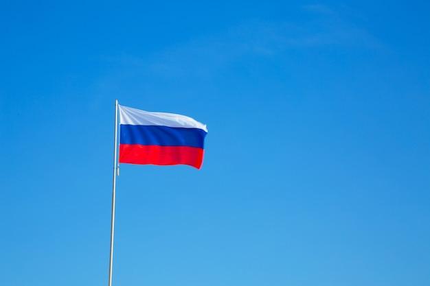 Российский флаг на шесте против голубого неба.