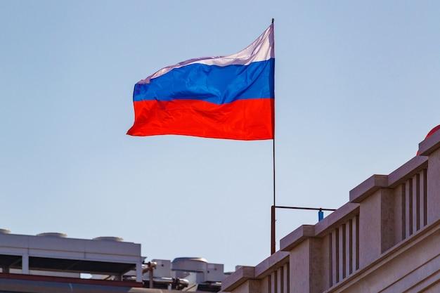 Российский флаг на флагштоке развевается на ветру против крыш зданий и голубого неба