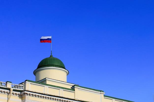 建物の屋上にロシア国旗。澄んだ青い空。