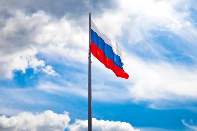 Российский флаг развевается против голубого неба