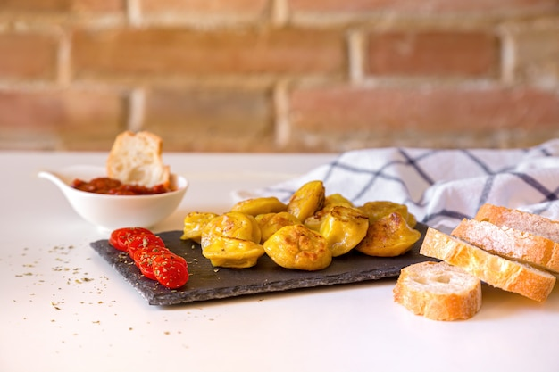 Russian food pelmeni, fried meat dumplings on stone plate, with tomates, bread and red sauce.